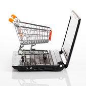 Compras en línea. carro de compras con cuaderno sobre el blanco — Foto de Stock