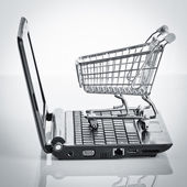 Shopping cart with notebook on the white. — Stock Photo