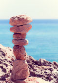 Balanced stones, pebbles stacks against blue sea  with a instagr — Stock Photo
