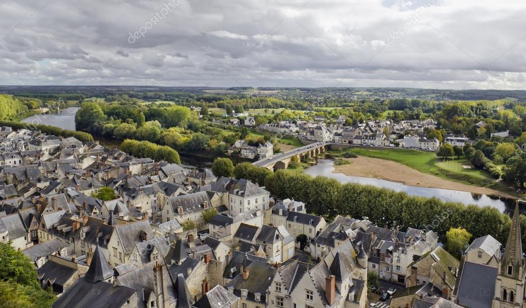 Panorama of the old French public domain standard town near the river and the forest. Tile roofs, stone bridge and narrow streets. Cloudy gray autumn day.   Foto Stock #16766847