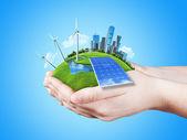 Las manos sosteniendo prado verde claro con batería solar, molino de aerogeneradores y los rascacielos de la ciudad — Foto de Stock