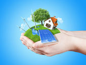Hands holding clear green meadow with sun battery block, wind mill turbines and countryside house — Stok fotoğraf