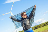 Girl holding canvas-cape and windturbine in background — Stock Photo