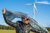 Dziewczynka gospodarstwa płótnie zielonego i windturbine w tle — Zdjęcie stockowe