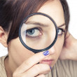 Girl with magnifying glass over her face — Stock Photo