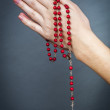 Rosary with female hand — Stock Photo