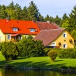 House in the middle of forest located by a lake — Stock Photo