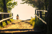 Girl walking through the forest pathway — Stock Photo