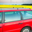 Stock Photo: Red car stands next to the field where rape flowers. and in the distance you can see the wind turbines