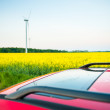 Red car stands next to the field where rape flowers. and in the distance you can see the wind turbines — Stock Photo #28071935