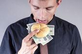 Podnikatel je jíst sendvič s penězi — Stock fotografie