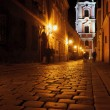 Street with church by night in Poznan - Stockfoto