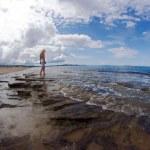 The girl on a rocky beach — Stock Photo #32580825