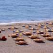 Parasols and sun loungers on the beach — Stock Photo