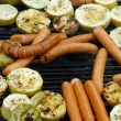 Grilling vegetables and sausages on pan — Stock Photo
