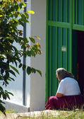 Image rurale avec la vieille femme assise en face de sa maison — Photo