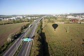 Aerial view of highway in the middle of fields, meadows and city — Stock Photo