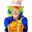 Stock Photo: Happy birthday clown with gift box.