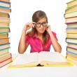 Woman student sitting at the desk surrounded with piles of books — Stock Photo