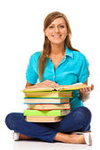 Happy student sitting on a floor with a stack of books — Stock Photo
