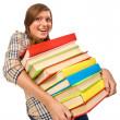 Teenage girl struggling with stack of books — Stock Photo