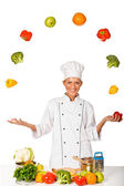 Woman chef juggling with fresh vegetables. Isolated — Stock Photo