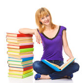 Lovely student sitting on a floor with stack of books, isolated — Stock Photo