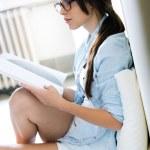 读一本杂志,坐在地上的女人 — 图库照片