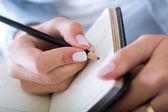 Mladá žena doma zapisování poznámek — Stock fotografie