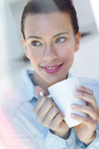 Young woman having a coffee at the kitchen — Stock Photo