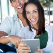 Young couple using a digital tablet — Stock Photo #29886901