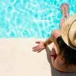 Stock Photo: Woman sitting in a swimming pool with a sunhat