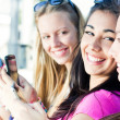 Three girls chatting with their smartphones — Stock Photo #30402953