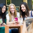 Three girls chatting with their smartphones — Stock Photo