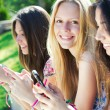 three girls chatting with their smartphones — Stock Photo #30406555