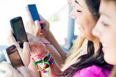 Tres chicas charlando con sus smartphones — Foto de Stock
