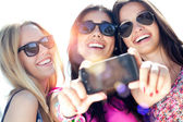 Three friends taking photos with a smartphone — Stock Photo