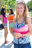Pretty student girl with some friends after school — Stock Photo