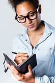 Young black woman taking notes at home — Stock Photo