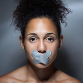 Black woman with mouth covered with tape — Stock Photo