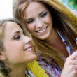 Two sisters with smartphone at the park — Stock Photo