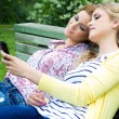 Stock Photo: Two sisters with smartphone at park