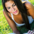 Young nice woman lies on green grass and reads book — Stock Photo
