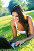 Portrait of beautiful woman in a park with laptop — Stock Photo