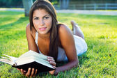 Young nice woman lies on green grass and reads book — Stock fotografie