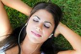 Frau hören musik auf gras liegend — Stockfoto