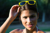 Portrait of a beautiful woman in a park with yellow sunglasses — Stock Photo