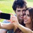 Happy young couple with smartphone at the park — Stockfoto