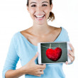 Happy young woman holding a digital tablet with a heart on the s — Stock Photo #32403795