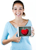 Happy young woman holding a digital tablet with a heart on the s — Stock Photo